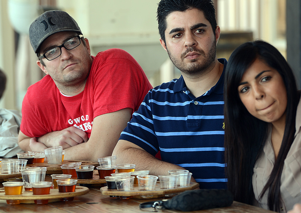 Description of . Joel Sheffer, 28, of Redlands, from the left, Navied Jabbari, 26, of San Jose and Brittany Jimenez, 25, of Mentone listen to a press conference at Hanger 24 Brewery, Tuesday December 17, 2013, where officials anounce Responsible Redlands. Local restaurants and businesses, like Hanger 24 Brewery and Redlands Cab Company, are teaming up with the City of Redlands, Redlands police department and the San Bernardino County District Attorney's office to help curb drunk driving in Redlands. From December 21, 2013 through January 1, 2014 Responsible Redlands will provide free rides home from local Redlands bar businesses, up to four miles. (Photo by Rick Sforza/Redlands Daily Facts)