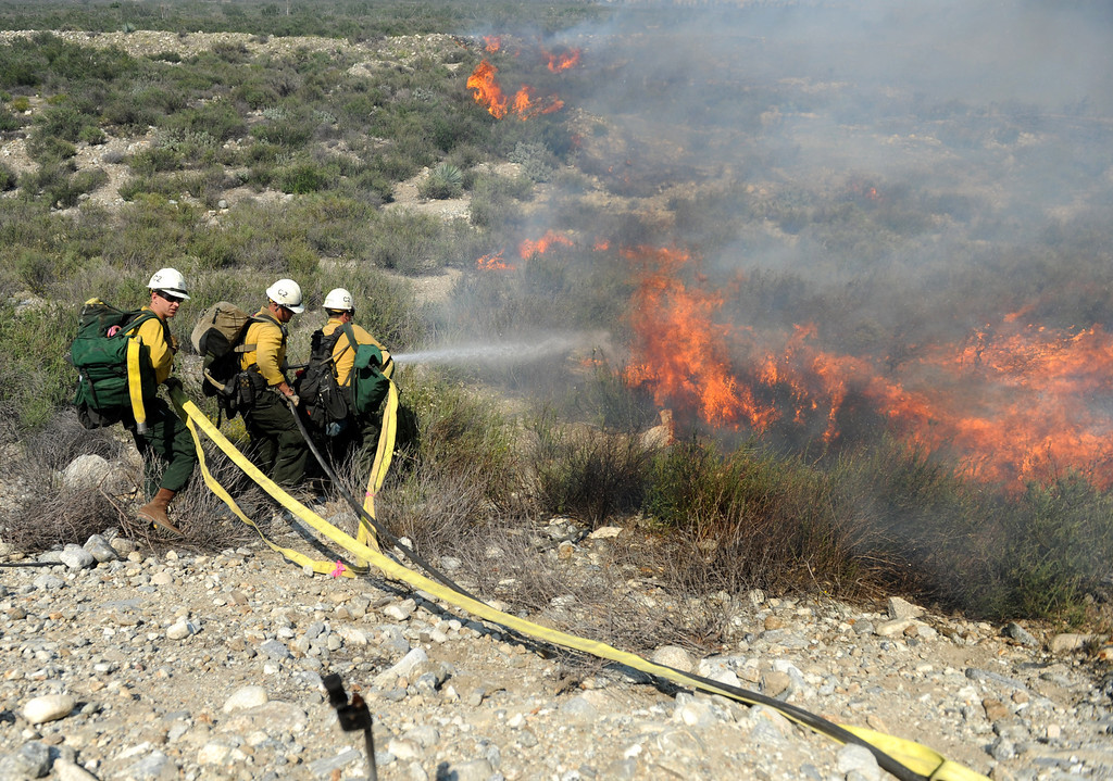 Description of . U.S. Forest Service Firefighters spray water on a hot spot just behind Los Osos High School as the Etiwanda Fire move through Rancho Cucamonga,Ca., Wednesday. The brush fire burned over 1,000 acres threatening homes, forcing esidents to evacuate and schools to close. (Photo by John Valenzuela/Inland Valley Daily Bulletin)