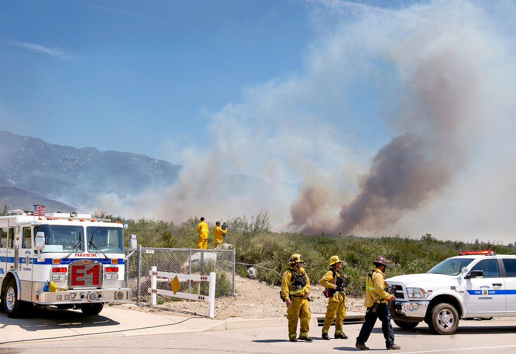 Description of . Smoke from the Etiwanda Fire looms behind firefighters staging on Wilson Avenue in Rancho Cucamonga, Calif. April 30, 2014.  (Staff photo by Leo Jarzomb/San Gabriel Valley Tribune)