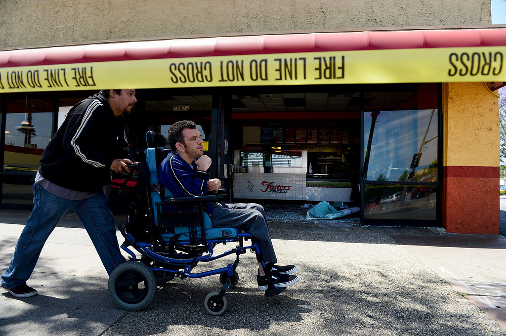 Description of . Christian Trasvina, of Temple City, wheels his client Terence past an El Pollo Loco with a Fosters Freeze on Valley Mall in El Monte Wednesday morning, May 15, 2013 after a vehicle crashed through a window following a collision at Santa Anita Boulevard. Trasvina was hoping to have lunch at the closed restaurant. (SGVN/Staff Photo by Sarah Reingewirtz)