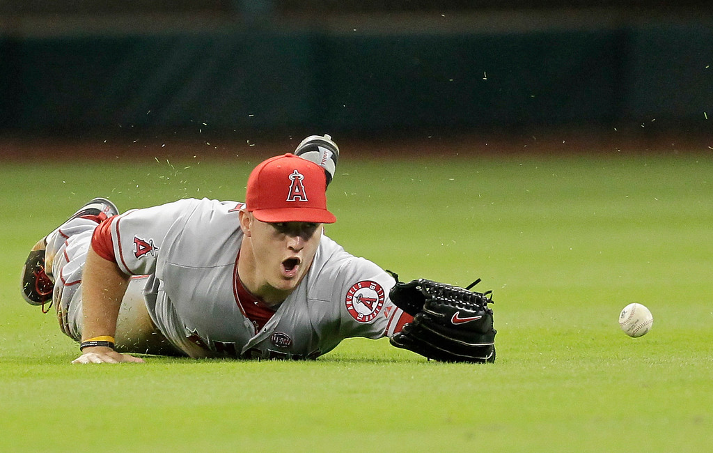 Description of . HOUSTON, TX - SEPTEMBER 14:  Mike Trout #27 of the Los Angeles Angels of Anaheim dives but can't make the catch on a shallow fly ball hit by Matt Dominguez #30 of the Houston Astros in the sixth inning at Minute Maid Park on September 14, 2013 in Houston, Texas.  (Photo by Bob Levey/Getty Images)