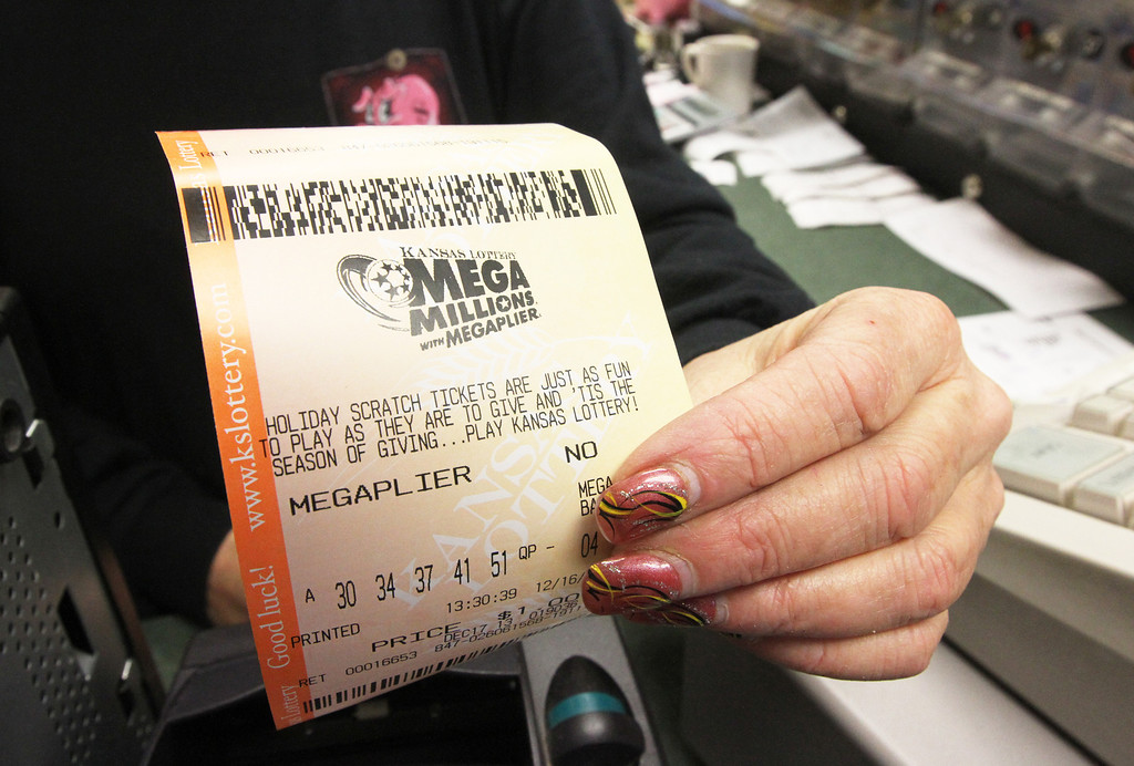 Description of . Fae Montgomery, a manager at the Heritage Restaurant in Wichita, Kan., sells a Mega Millions ticket Monday Dec. 16, 2013.  The Mega Millions jackpot soared on Monday amid a frenzy of ticket purchases, a jump that pushed the prize closer to the $656 million U.S. record set last year. (AP Photo/Wichita Eagle, Brian Corn)