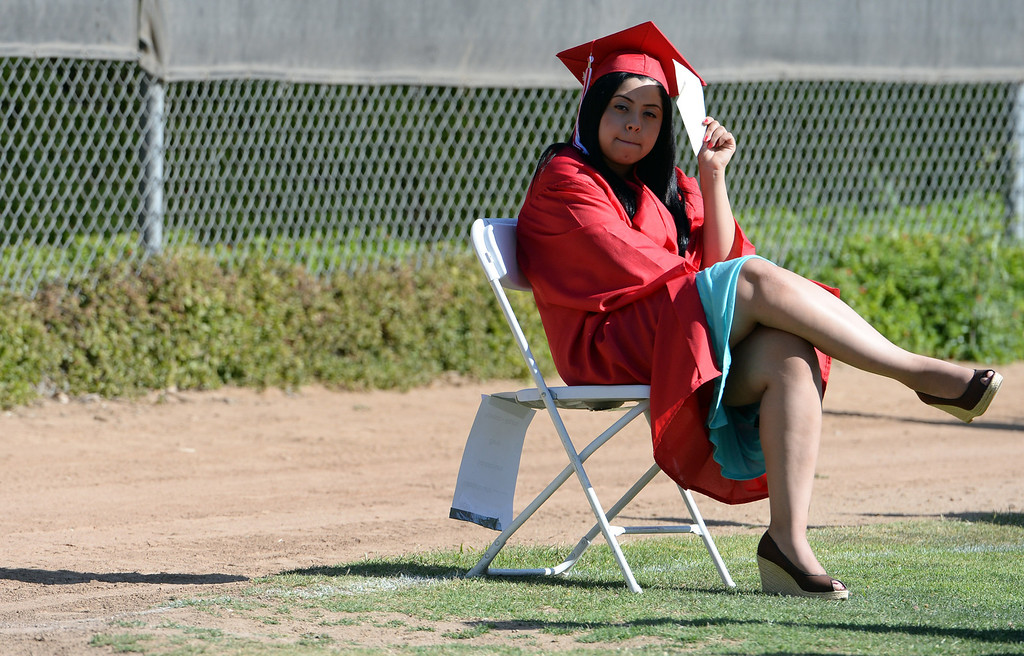 Description of . A student shields her face from the sun prior to the Whittier High School graduation at Whittier College in Whittier, Calif., on Wednesday, June 4, 2014.  (Keith Birmingham/Pasadena Star-News)