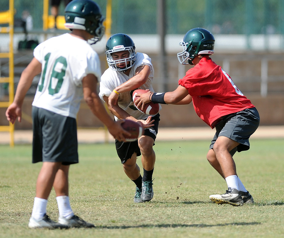 Description of . QB Garrett Fonseca, right, hands off during morning practice at South Hills High School on Friday, Aug. 9, 2013 in West Covina, Calif.   (Keith Birmingham/Pasadena Star-News)