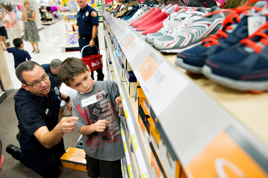 Description of . Brandon Ryan, 6, looks for new pair of shoes as he shops with an LA County firefighter at Target in San Dimas on Tuesday, Sept. 10, 2013. Volunteers from the Soroptimists club, as well as the RSVP (retired senior volunteer patrol) of La Verne PD, Los Angeles County Sheriff's Department and Los County firefighters all paired up with a student from Bonita Unified elementary to take them shopping and find clothes and shoes. (Photo by Watchara Phomicinda/ San Gabriel Valley Tribune)