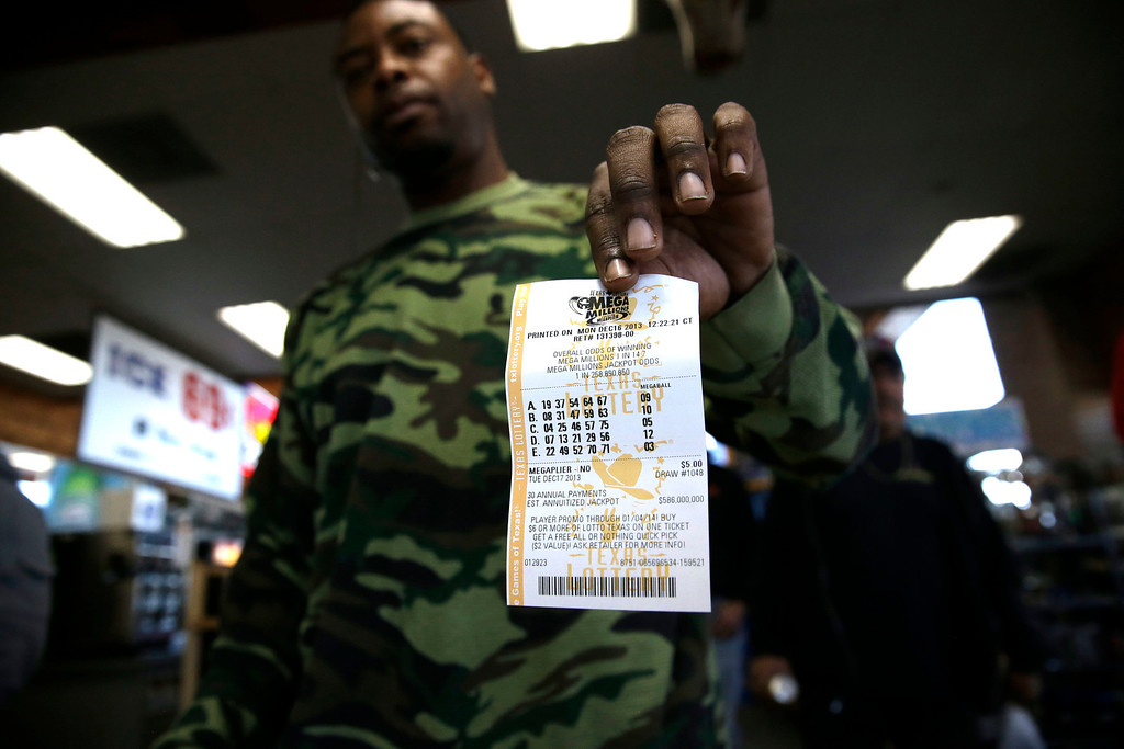 Description of . John Hollis shows off his Mega Millions lottery ticket he purchased at the Fuel City convenience story Monday, Dec. 16, 2013, in Dallas. The Mega Millions jackpot soared to $586 million on Monday amid a frenzy of ticket purchases, a jump that pushed the prize closer to the $656 million U.S. record set last year. (AP Photo/LM Otero)