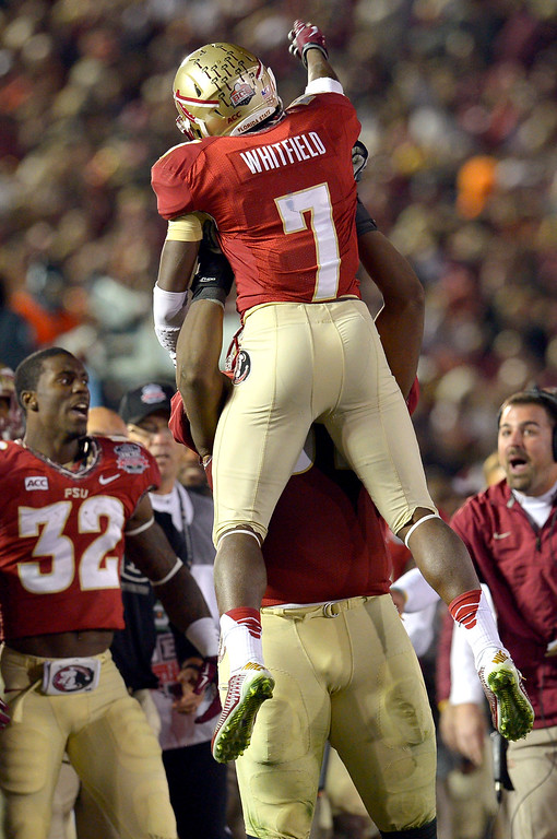 Description of . Florida State's Kermit Whitfield is hoisted in the air after returning a kickoff for a touchdown against Auburn during the 2014 Vizio BCS National Championship January 6, 2014 in Pasadena CA.  Florida State won the game 34-31.(Andy Holzman/Los Angeles Daily News)