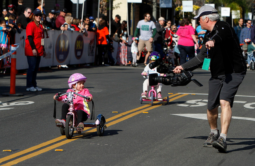 Description of . Sarah Horter, 4, left, watches cameraman David Huot as she participates in the public race portion of the Redlands Bicycle Classic on Saturday, April 5, 2014 in Redlands, Ca. (Photo by Micah Escamilla for the Redlands Daily Facts)