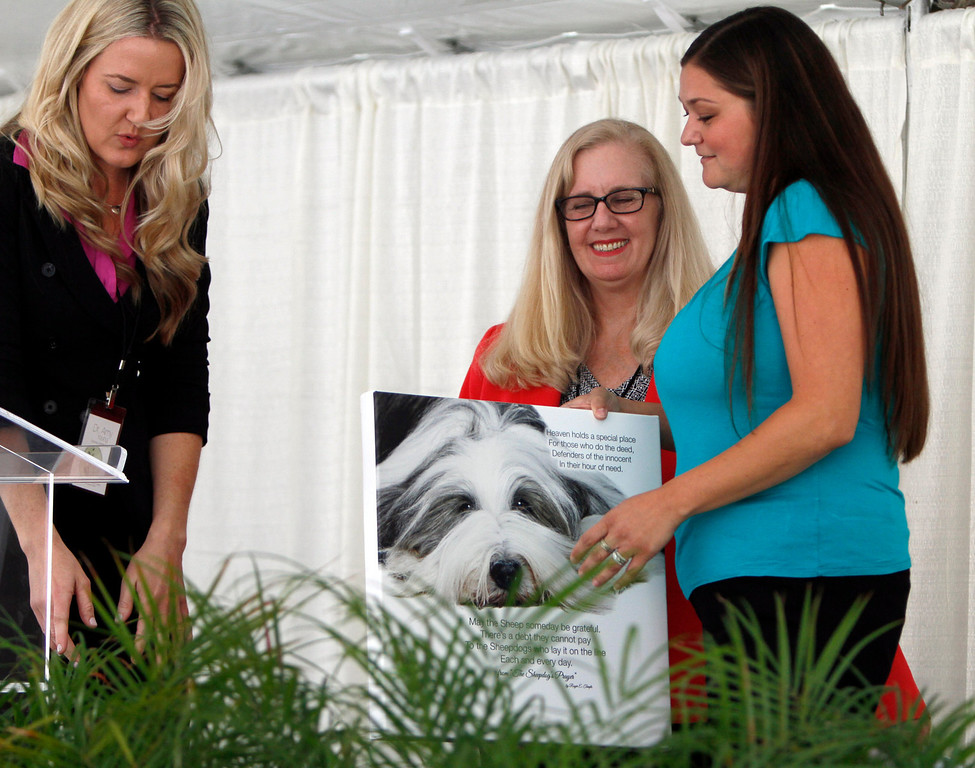 Description of . Dr. Amy Young, left, and Nancy Wolfe, center, both of the Children's Assessment Center, present Lynette MacKay, wife of slain San Bernardino County Sheriff's Deputy Jeremiah MacKay, with a photo created in memory of her husband during a dedication ceremony in his memory on Wednesday, May 21, 2014 at the Children's Assessment Center in San Bernardino, Ca. An entire wing of the assessment center has been dedicate to Deputy MacKay.(Photo by Micah Escamilla/San Bernardino Sun)