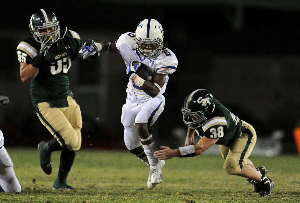 Description of . Charter Oak's Zion Echols (6) runs through the defense of South Hills' Ryan Rodriguez (55) and Mason Behr (38) in the first half of a prep football game at Covina DIstrict Field in Covina, Calif., on Thursday, Oct. 24, 2013. 