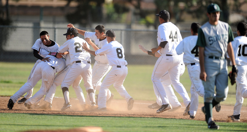 Description of . Northview's Kollby Oriti is mobbed by teammates after walking with the bases loaded as teammate Alex Labor (not pictured) scores the winning run in the bottom of the seventh inning to defeat South (Torrance) 5-4 during a CIF-SS prep second round playoff baseball game against South (Torrance) at Northview High School on Tuesday, May 21, 2013 in Covina, Calif. 