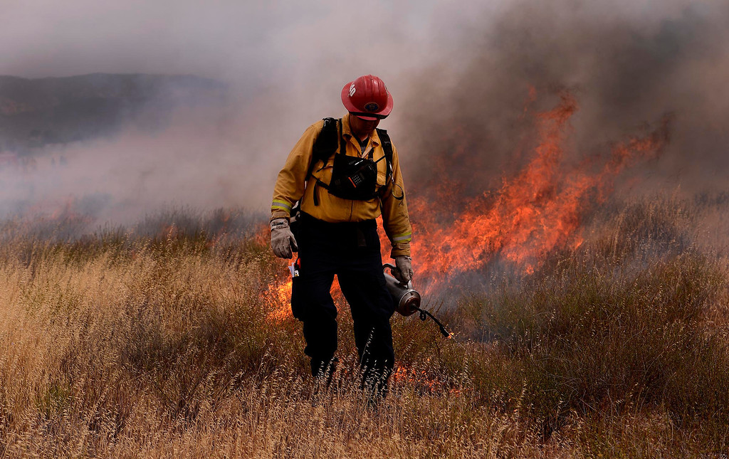 Description of . A firefighter uses a drip torch to light a section of vegetation during a training fire along Sierra Avenue north of Summit Avenue in North Fontana May 23, 2013.   GABRIEL LUIS ACOSTA/STAFF PHOTOGRAPHER.