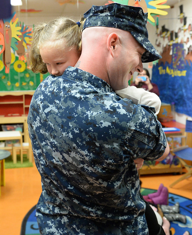 Description of . Navy Chief Nick Elliot hugs his daughter Alexis, 4, after surprising her inside her classroom at First Lutheran Children's Center in Redlands,CA. Thursday, Nov. 21, 2013. Elliots was deployed overseas for eight months, serving in the Persian Golf on the USS Harry S. Truman, this has been the longest he has ever been away from his family. (John Valenzuela/Staff Photographer)