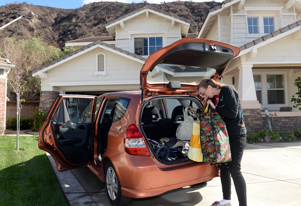 Description of . Amanda Hartrell loads up her vehicle as she prepares to evacuate from her home on Ridge View Drive in case the mud from the hills behind their home slides down in Azusa on Thursday February 27, 2014. (Staff Photo by Keith Durflinger/San Gabriel Valley Tribune)