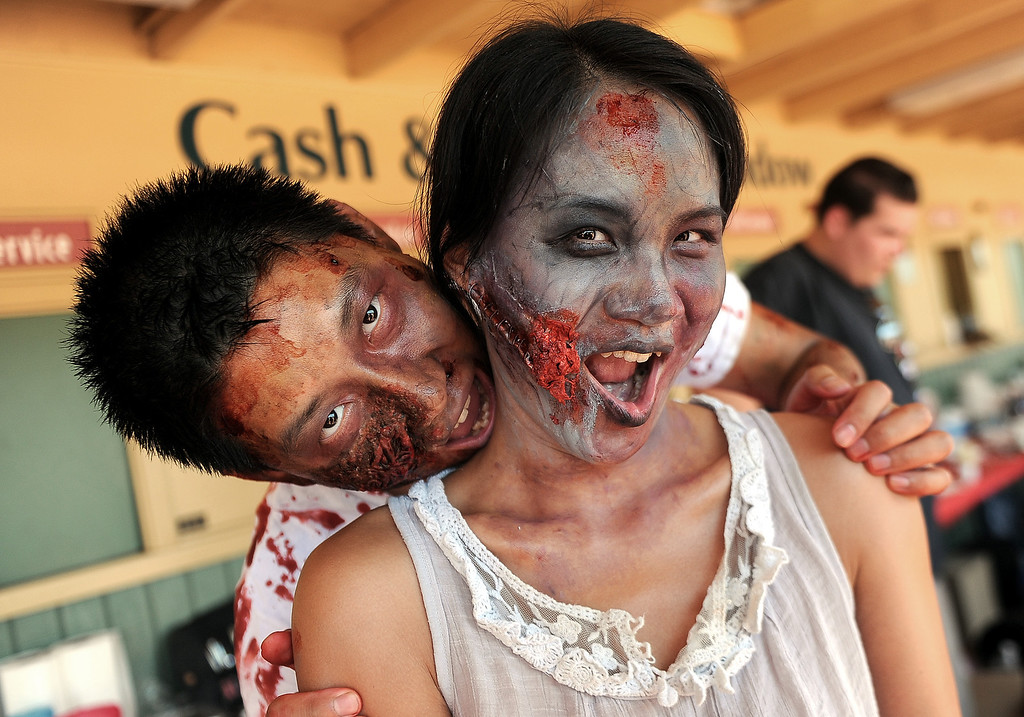 Description of . Vincent, left, Zou with his wife Yiji Zou of Hacienda Heights after having zombie make-up applied during the Zombie Blood Run at Santa Anita Park on Saturday, Aug. 17, 2013 in Arcadia, Calif. The American Red Cross San Gabriel Pomona Valley chapter is partnering with the Zombie Blood Run to prepare the San Gabriel Valley for a disaster, even a zombie apocalypse.  (Keith Birmingham/Pasadena Star-News)