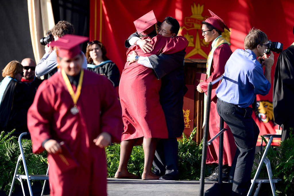 Description of . Patricia Monyei, a district scholar, celebrates after  receiving her diploma by hugging Principal Frank Chang during Wilson High School's forty-seventh commencement ceremony Tuesday evening, May 20, 2014 at the Hacienda Heights school. (Photo by Sarah Reingewirtz/Pasadena Star-News)