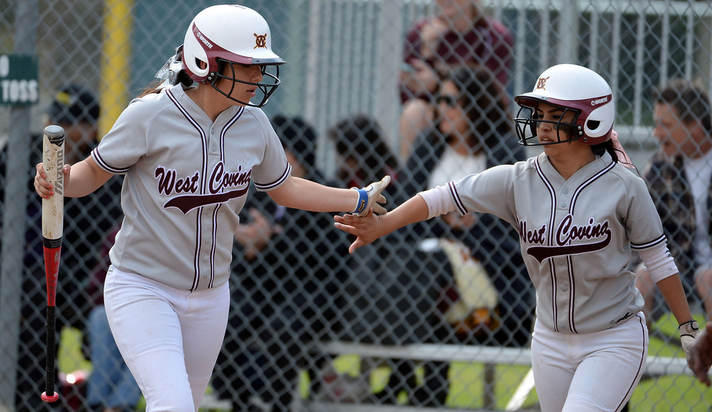 Description of . West Covina's Isabella Montoya, left, high fives Nadiya Lozano (C), right, after scoring in the first inning of a prep softball game against Bonita at Los Flores Park in La Verne, Calif., on Thursday, March 27, 2014. Bonita won 6-3. (Keith Birmingham Pasadena Star-News)