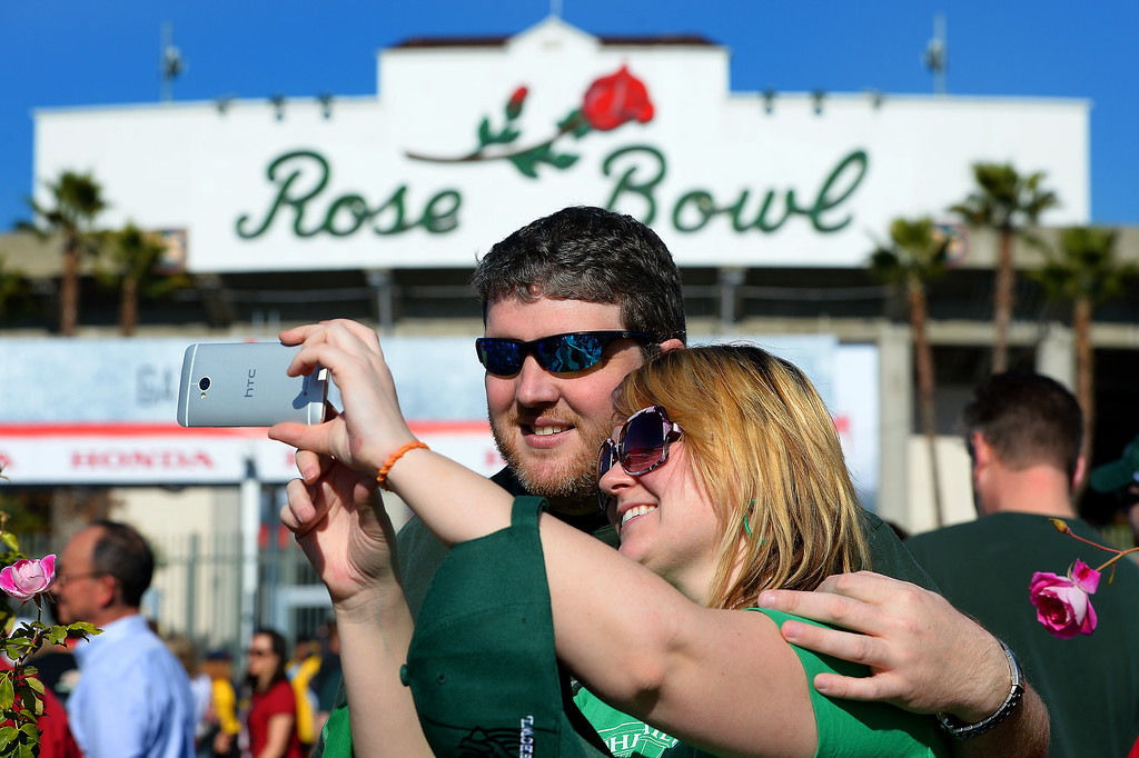 Description of . Michigan State fans Rich LaPratt and Emily Stuart take a picture in front of the Rose Bowl, Wednesday, January 1, 2014. (Photo by Michael Owen Baker/L.A. Daily News)