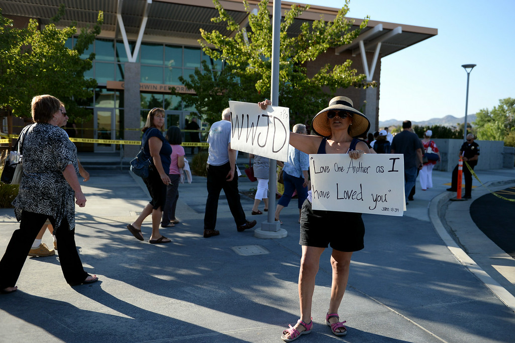 Description of . Andrea Tokunaga, 50, of Murrieta, holds signs outside a town hall meeting on Wednesday, July 2, 2014 at Murrieta Mesa High School in Murrieta, Ca. The meeting is being held in response to immigrants who were being processed through a Texas Border Patrol Station and delivered to the Murrieta Border Patrol Station on Tuesday, which created protests from both sides of the immigration issue. (Micah Escamilla/The Sun)