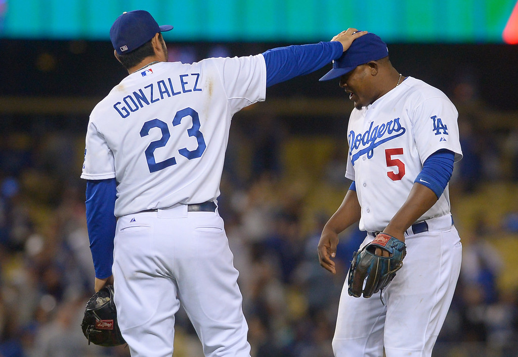 Description of . Juan Uribe gets a pat from Adrian Gonzalez after the Dodgers beat the Arizona Diamondbacks 8-1 Monday, September 9, 2013.  Uribe hit 3 homeruns in the game.  (Andy Holzman/Los Angeles Daily News)
