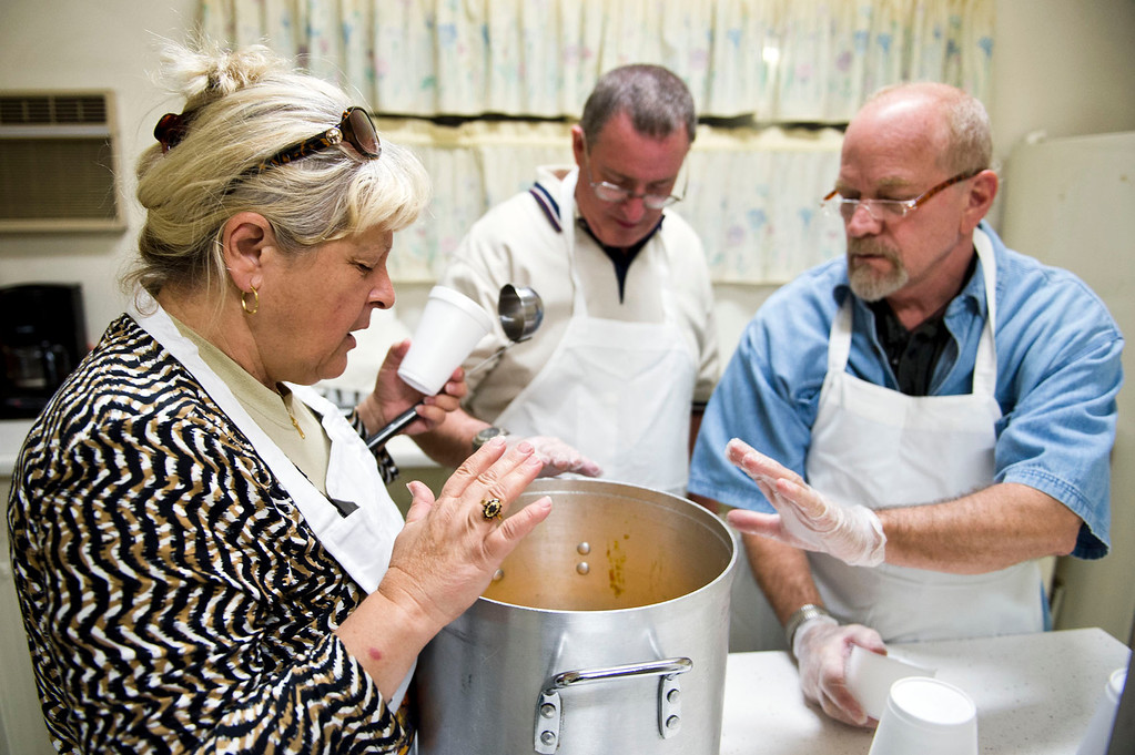 Description of . From left, Nicolette Wingert, Phillip Stern and Christopher Barns say a prayer before distributing the soup at the Church of the Brethren kitchen in Glendora on Wednesday night, Nov. 27, 2013. Nicolette Wingert has been feeding the homeless six days a week for the past seven years with Nurses4Christ, a nonprofit organization she founded in 2006. (Photo by Watchara Phomicinda/San Gabriel Valley Tribune)