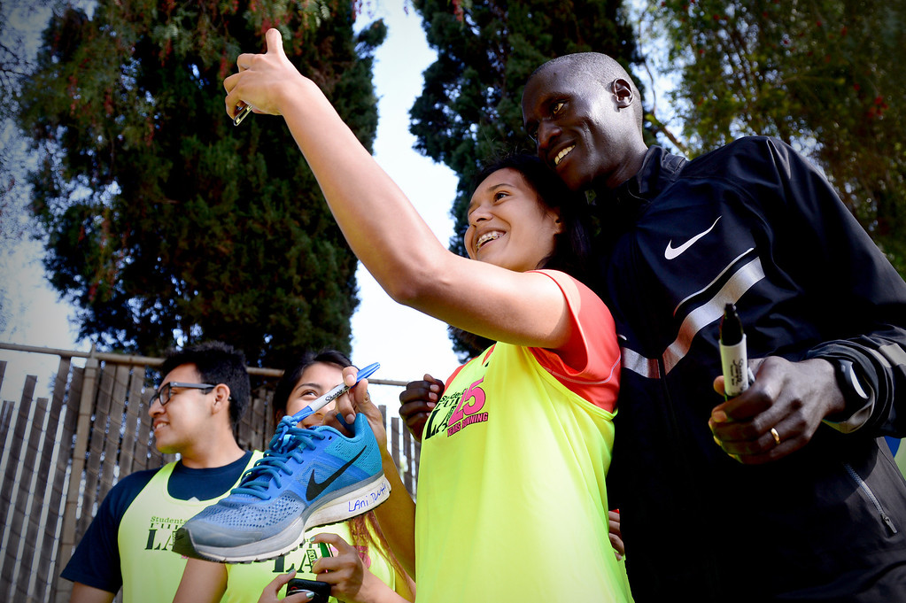 Description of . Joselin Rivas, 17, of Foshey Learning Center, takes a selfie with elite marathon runner Lani Rutto, of Kenya, as he signs shoes and jerseys for students of Students Run LA program Friday, March 7, 2014 in Griffith Park. Elite marathon runners were training at the park for Sunday's LA Marathon before visiting with the students, who also will be running in Sunday's marathon. (Photo by Sarah Reingewirtz/Pasadena Star-News)