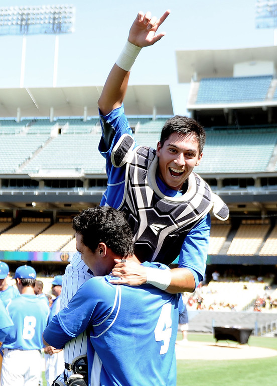 Description of . Bishop Amat's Michael Palos jumps into the arms of teammate Alex Garcia (4) as they defeated Palm Desert 4-3 to win the CIF-SS Division 3 baseball championship at Dodger Stadium in Los Angeles on Friday, June 6, 2014.   (Keith Birmingham/Pasadena Star-News)