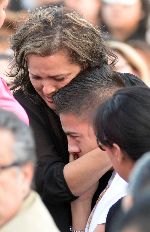 Description of . Veronica Soriano, mother of Adrian Castro, 19,hugs one of the bus crash survivors before a memorial gathering for him at El Monte High School Monday evening April 14, 2014. Castro was one of nine students killed in the bus crash in Orland, Calif. (Staff Photo by Keith Durflinger/San Gabriel Valley Tribune)