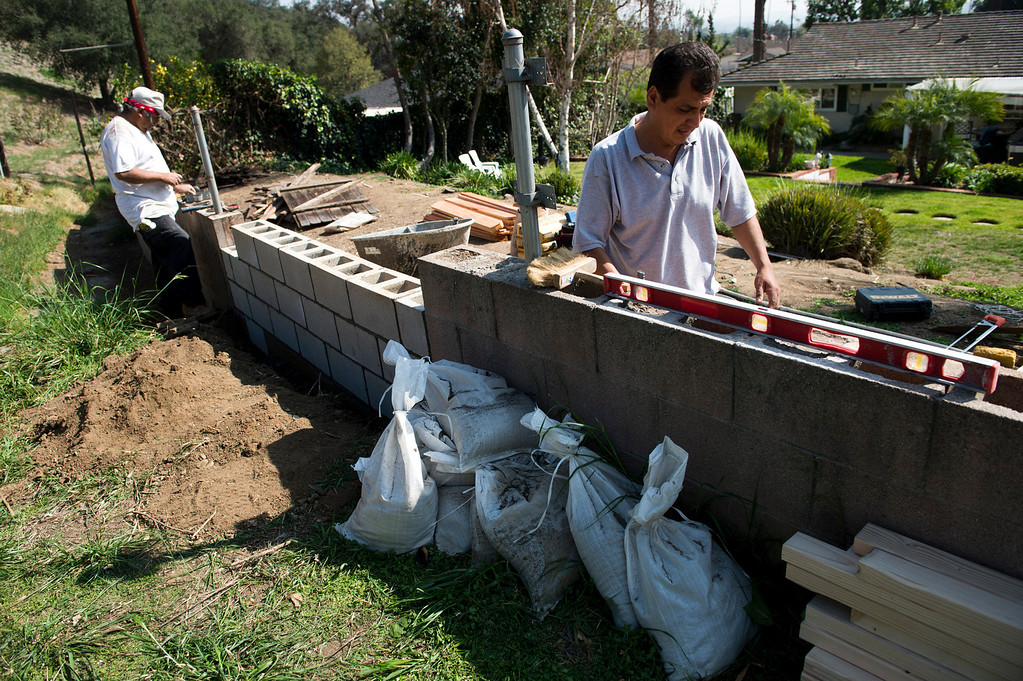 Description of . Construction workers build a wall in the 1000 block of Becklee Road on Tuesday, Feb. 25, 2014 as Glendora residents prepare for two major rainstorms that will hit the region this week that potentially will cause mudslides in the area devastated by the Colby Fire. (Photo by Watchara Phomicinda/ San Gabriel Valley)