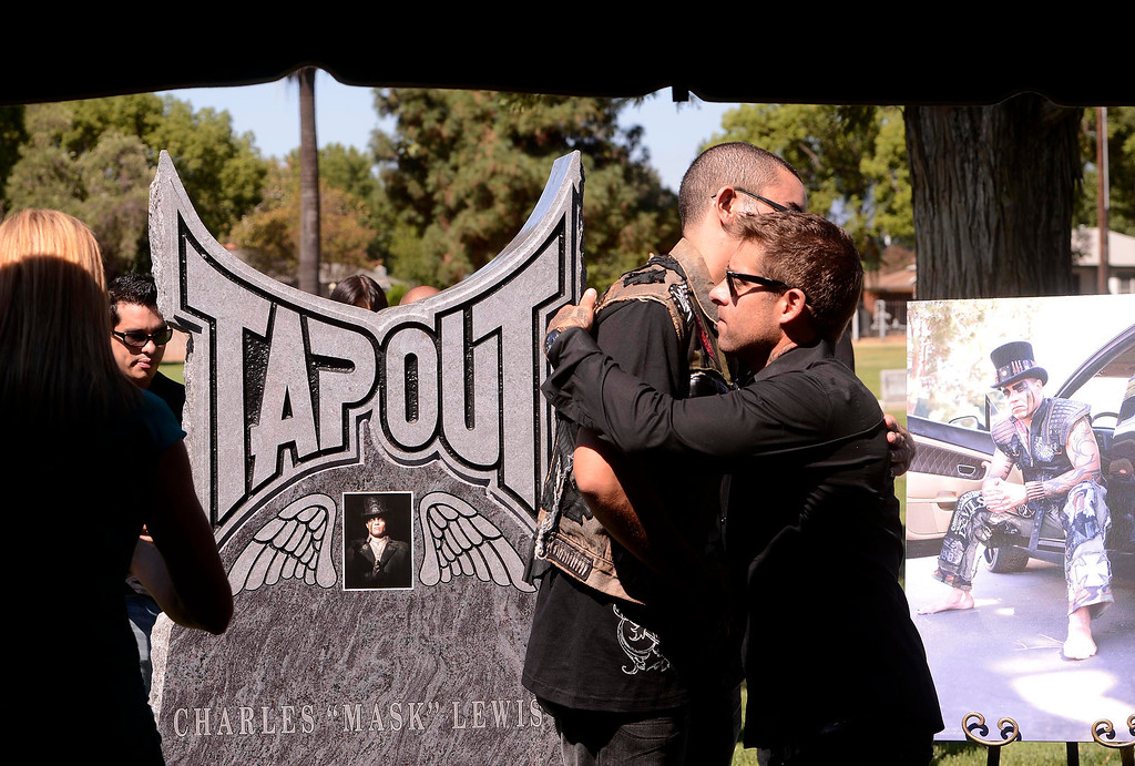 Description of . Boaz Lewis, 20, of Riverside, center left, is hugged by Tapout president and co-founder Dan Caldwell during a tribute for Charles Lewis Jr. at Mountain View Cemetery in San Bernardino, CA on Saturday September 7, 2013.  Lewis was killed by a drunk driver in March of 2009.  (Photo by Gabriel Luis Acosta/San Bernardino Sun)