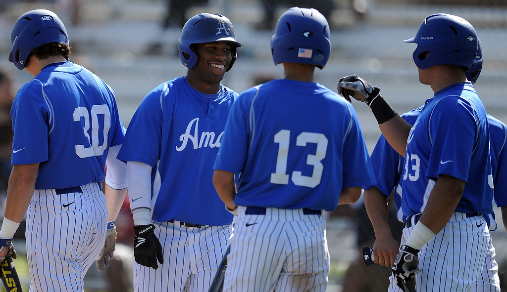 Description of . Bishop Amat's Daryl Daniels, center, smiles after scoring in the third inning of a CIF-SS Division 3 first round playoff baseball game against Santiago at Bishop Amat High School on Wednesday, May 15, 2013 in La Puente, Calif. Bishop Amat won 12-3.  (Keith Birmingham Pasadena Star-News)