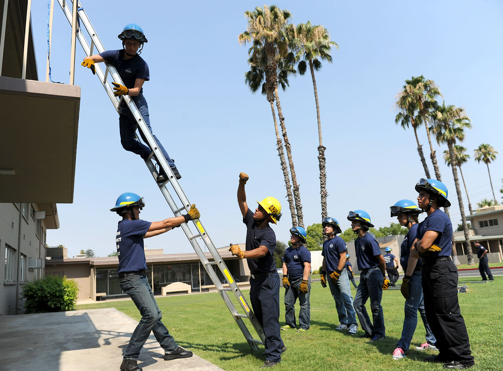 Description of . (John Valenzuela/Staff Photographer) Firefighter Jesse Sparks gives instruction to Redlands Emergency Services Academy students during ladder training at the University of Redlands, Thursday, July 18, 2013.