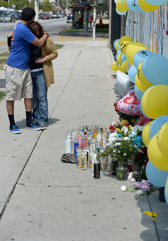 Description of . Andrew and his mother Ruth Escalera are emotional as they look at the memorial. Andrew graduated last year from the rival high school, South El Monte H.S. Students at El Monte High School brought flowers, candles and other items in remembering Adrian Castro, a Senior student who was killed in bus crash in Northern California that took the lives of 10 people. El Monte, CA. 4/13/2014(Photo by John McCoy / Los Angeles Daily News)