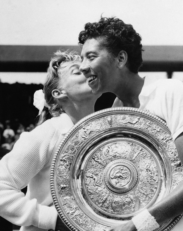 Description of . FILE - In this July 6, 1957 file photo, Althea Gibson, of New York City, holds the women\'s singles tennis trophy at Wimbledon, England, while being kissed by her finals opponent, Darlene Hard, of Montebello, Calif. (AP Photo, File)