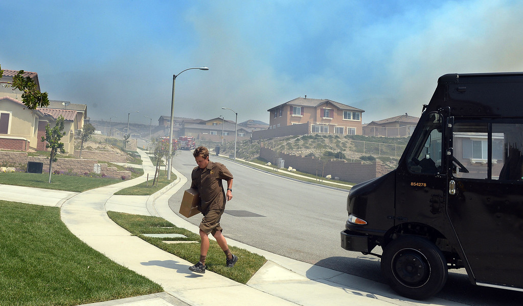 Description of . A United Parcel Service driver runs to drop off a package at a home under evacuation in Rancho Cucamonga Wednesday. Over 1,000 acres and over a 1,000 homes are under mandatory evacuation as the Etiwanda Fire burns in Rancho Cucamonga Wednesday April 30, 2014. Cause of the fire is unknown and is burning in areas which burned during the Grand Prix Fire in October 2003. (Will Lester/Inland Valley Daily Bulletin)