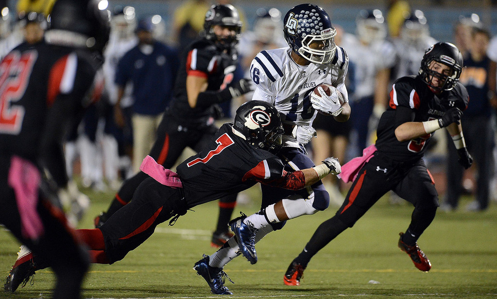 Description of . Los Osos' Donovan Williams (16) runs for a first down as Glendora's Collin Grady (7) makes the tackle in the first half of a prep football game at Citrus College in Glendora, Calif., on Thursday, Oct. 31, 2013.    (Keith Birmingham Pasadena Star-News)