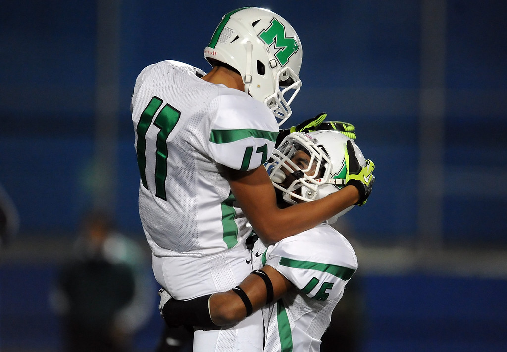 Description of . Monrovia's Kahlil Bradley (17) jump into the arms of his teammate Jordan Nathan (16) after catching a pass for a touchdown against San Marino in the first half of a prep football game at Monrovia High School in Monrovia, Calif., on Friday, Nov. 8, 2013. 