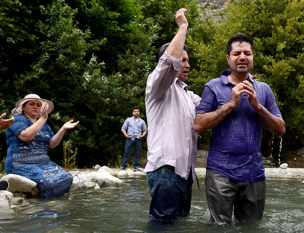 Description of . Pastor Jesus Rodriguez, of Iglesia del Dios Vivo in La Puente, baptizes Enrique Estrada, of La Puente, in the San Gabriel River along the East Fork of the Angeles National Forest Saturday, July 20, 2013. The Urban Conservation Corps educates people visiting the East Fork of the San Gabriel River in the Angeles National Forest. Although the Urban Conservation Corps says their river trash count studies show less trash the area is still littered with garbage. (SGVN/Staff Photo by Sarah Reingewirtz)
