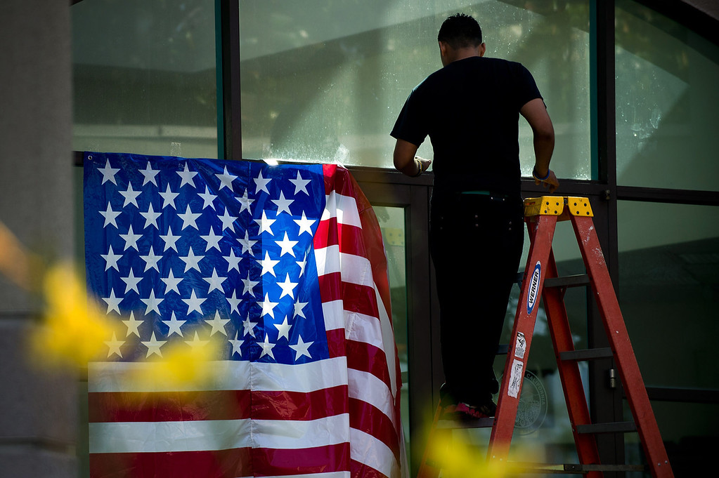 Description of . A worker puts up an American flag in front of Palm Park Aquatic Center  during the 4th of July celbration in Whittier on Thursday, July 4, 2013. (SGVN/Staff photo by Watchara Phomicinda)