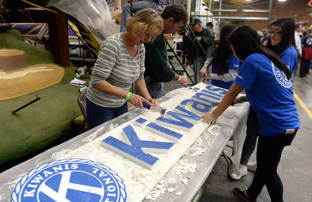Description of . Volunteers work on the Kiwanis float during the final stages of preparation for the 2014 Rose Parade as a variety of seeds, bark, fruits and vegetables, grasses and of course, flowers are being applied to the floats by experienced professionals as well as hard working volunteers at the Rosemont Pavilion in Pasadena, Calif., on Saturday, Dec. 28, 2013.     (Keith Birmingham Pasadena Star-News)