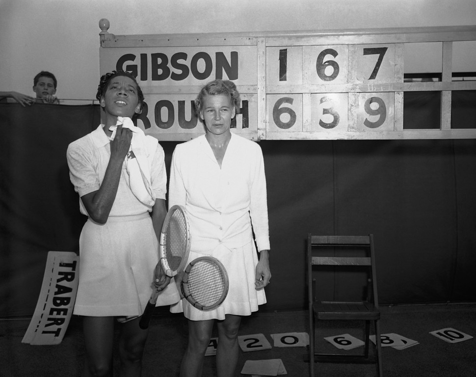 Description of . Tennis player Althea Gibson, left, of New York, wipes her face as she stands with Louise Brough, of Beverly Hills, Calif., who eliminated Gibson in the second round match of the National Tennis Championships in Forest Hills, New York, Aug. 30, 1950. Brough, Wimbledon champion, won 6-1, 3-6, 9-7. Gibson, the first African American ever to play in the event, led by seven games to six when play resumed in the third set of the match, which was rained out the day before. (AP Photo)