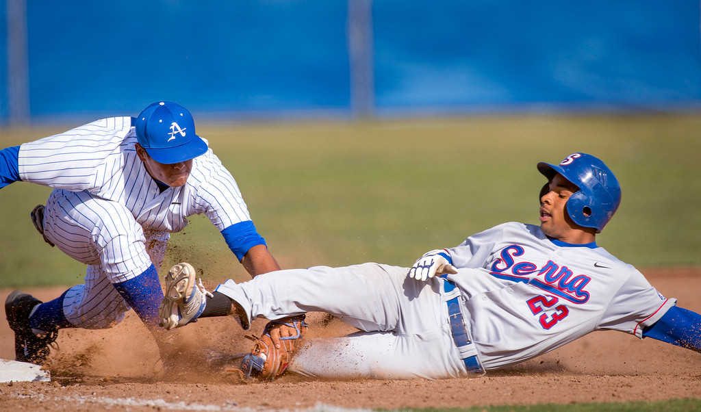 Description of . Bishop Amat's 3B Jayson Gonzalez, left, tags out Serra High's Denz'l Chapman trying to stretch a triple in the sixth inning at Amat's La Puente, Calif. campus field April 16, 2014.  (Staff photo by Leo Jarzomb/San Gabriel Valley Tribune)