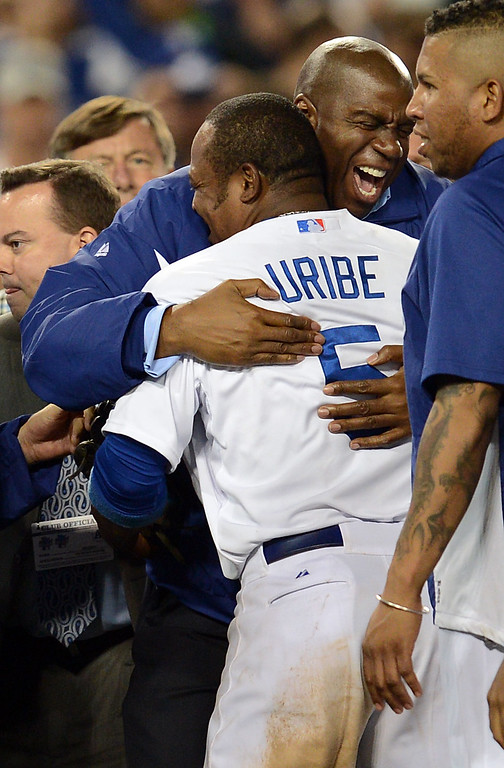 Description of . Dodgers' owner Magic Johnson hugs Juan Uribe after the final out against  the Atlanta Braves during game 4 of the NLDS at Dodger Stadium Monday, October 7, 2013. The Dodgers beat the Braves 4-3.(Photo by Hans Gutknecht/Los Angeles Daily News)