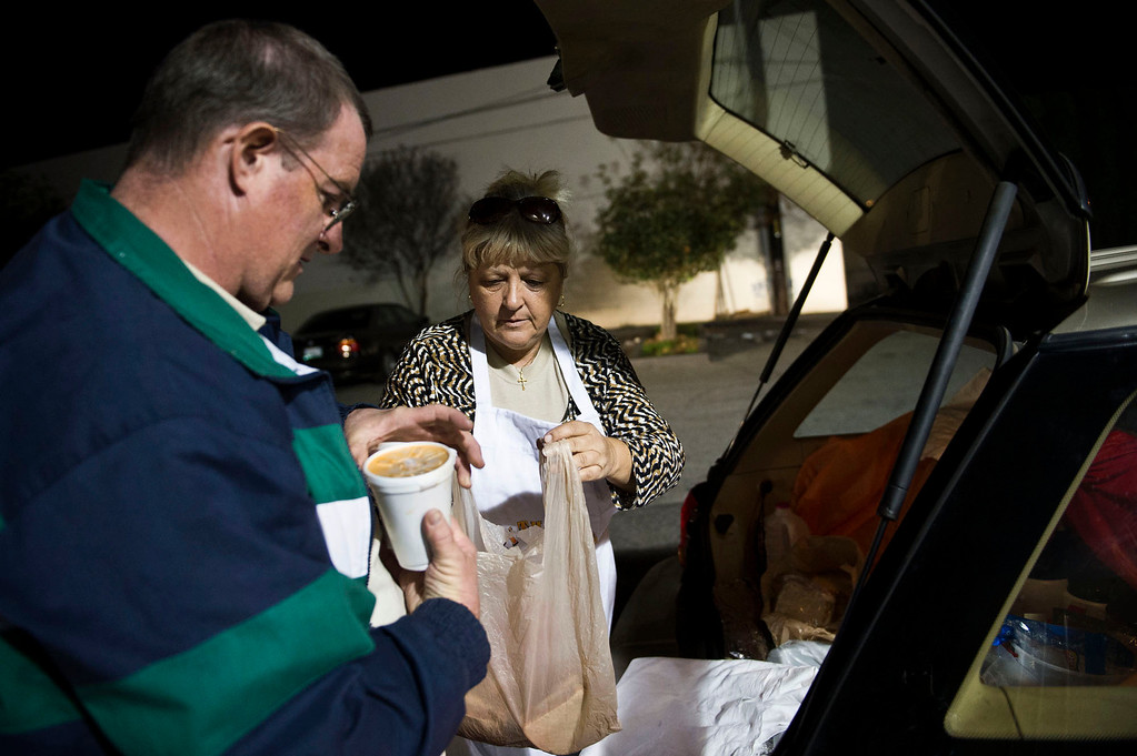 Description of . Nicolette Wingert and Phillip Stern grab meals from the car to distribute to the homeless people in Covina on Wednesday night, Nov. 27, 2013. Nicolette Wingert has been feeding the homeless six days a week for the past seven years with Nurses4Christ, a nonprofit organization she founded in 2006. She and Phillip Stern of Glendora have been going every day since 2008, feeding homeless people sandwiches and hot food; giving them bottles of water, clothes and blankets. (Photo by Watchara Phomicinda/San Gabriel Valley Tribune)
