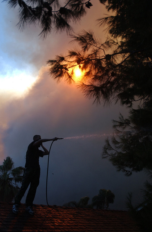 Description of . Ten years ago this month the arson caused Old Fire, fanned by Santa Ana winds burned thousands of acres, destroyed hundreds of homes and caused six deaths. The fire burned homes in San Bernardino, Highland, Cedar Glen, Crestline, Running Springs and Lake Arrowhead and forced the evacuation of thousand of residents.  A man stands on his home trying to water down his roof as the Old Fire burns in San Bernardino. (Staff file photo/The Sun)