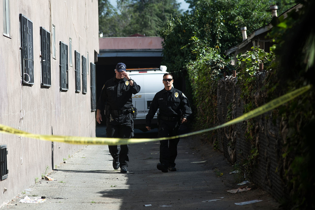 Description of . Police investigate an early morning shooting death of a woman in an apartment complex in the 700 block of San Francisco Avenue in Pomona on Monday, June 14, 2014. The body was found in the carport area behind the complex. (Photo by Watchara Phomicinda/ San Gabriel Valley Tribune)