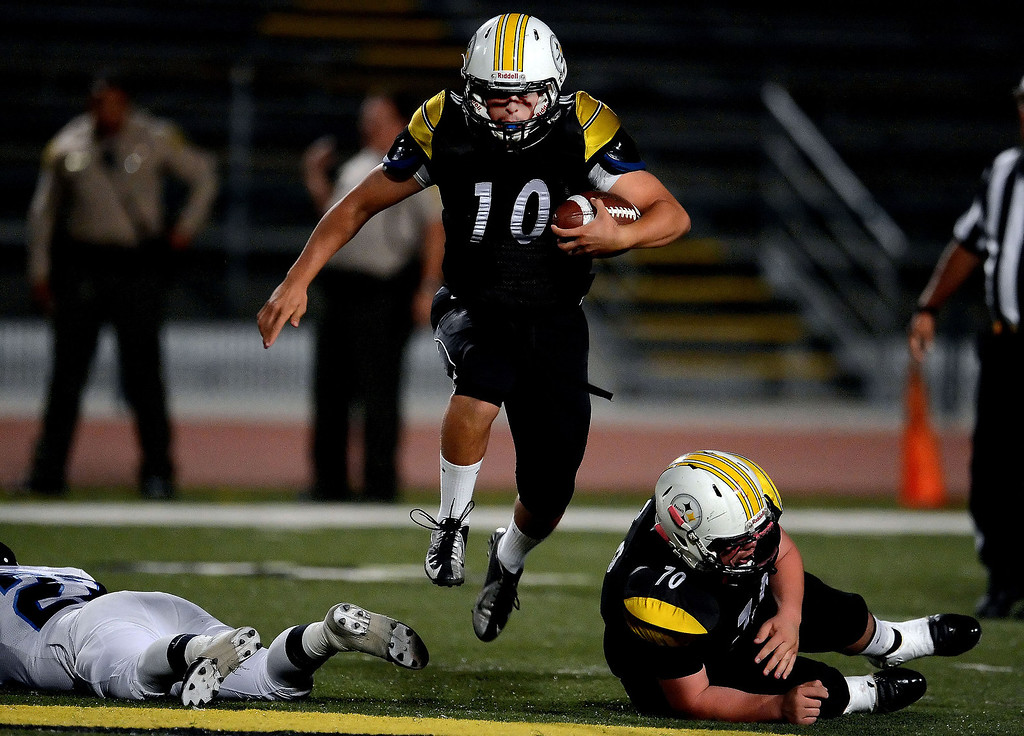 Description of . Bassett quarterback Nicolas Colmenero (10) runs for a first down against Duarte in the first half of a prep football game at Bassett High School in La Puente, Calif., on Friday, Nov. 1, 2013.    (Keith Birmingham Pasadena Star-News)