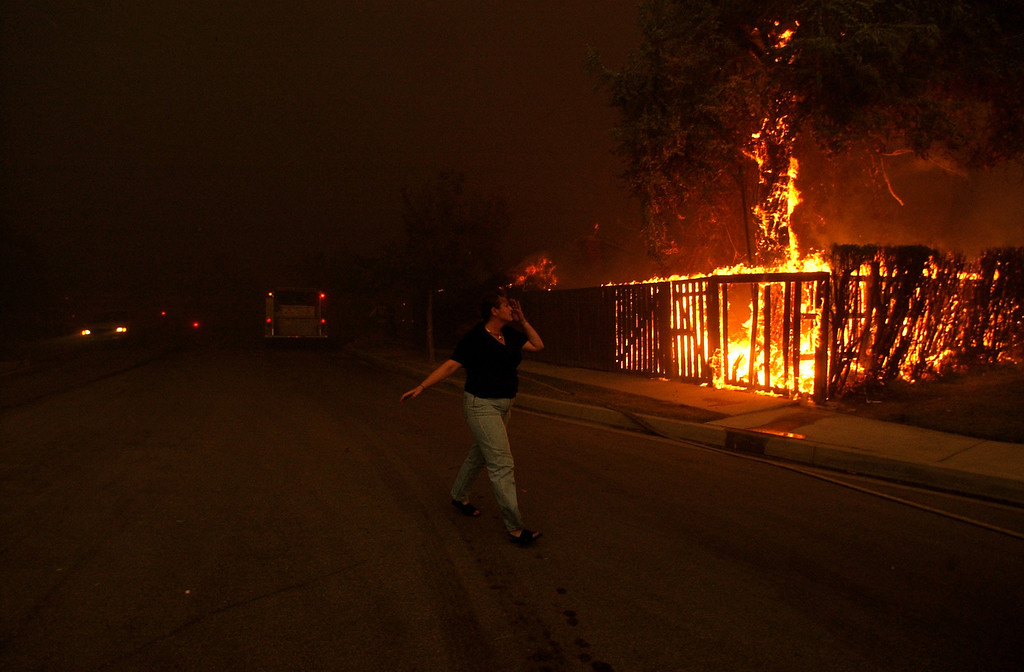 Description of . Ten years ago this month the arson caused Old Fire, fanned by Santa Ana winds burned thousands of acres, destroyed hundreds of homes and caused six deaths. The fire burned homes in San Bernardino, Highland, Cedar Glen, Crestline, Running Springs and Lake Arrowhead and forced the evacuation of thousand of residents. An unidentified woman runs along Sonora Road at Golden Avenue as she waits for firefighters to save her property in north San Bernardino. (Staff file photo/The Sun)