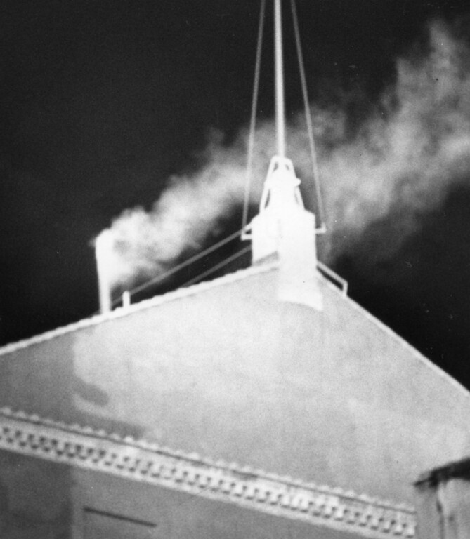 Description of . FILE - This Oct. 16, 1978 file photo shows white smoke pouring out of the chimney atop the Sistine Chapel at 18.18 local time indicating that the conclavists have elected a successor to late Pope John Paul I. Cardinal Karol Wojtyla, archbishop of Krakow, Poland, was elected pontiff and took the name of Pope John Paul II. The papal conclave is steeped in mystery — and the church likes it that way. Elaborate ritual and veils of secrecy, after all, are fundamental to the papal mystique, seen as the glue the binds worshipers in faith. (AP Photo)