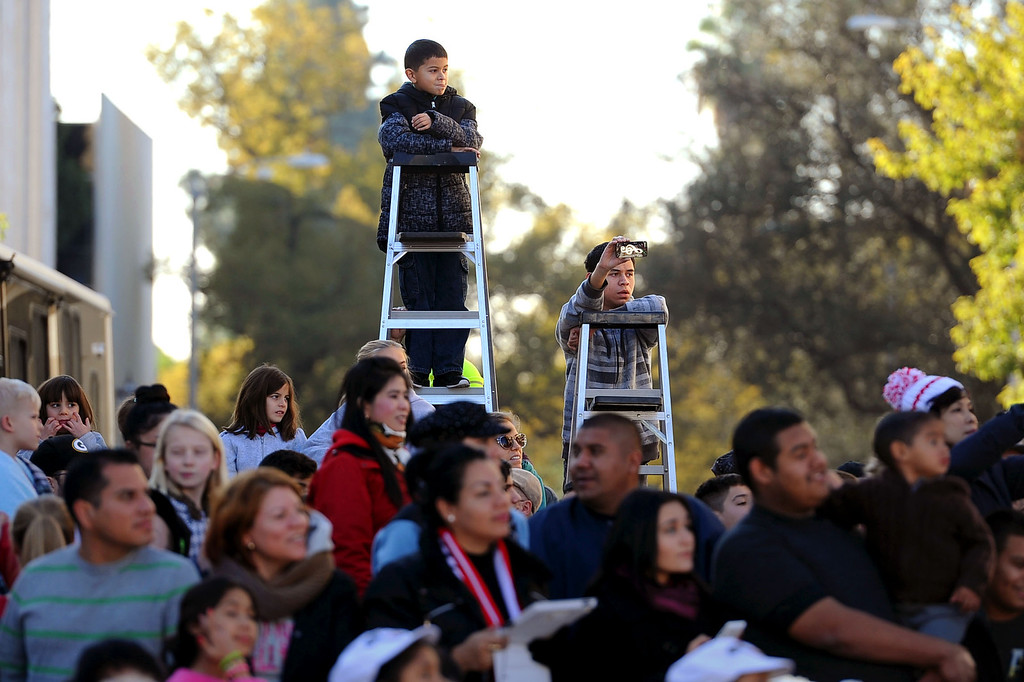 Description of . Youngsters use ladders to watch the 2014 Rose Parade in Pasadena, CA January 1, 2014.(Andy Holzman/Los Angeles Daily News)